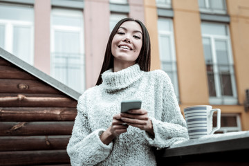 Joyful positive woman standing with her phone
