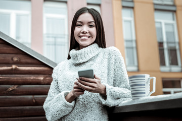 Cheerful attractive woman using her new gadget
