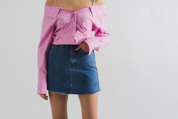 Young slim girl in short blue denim skirt and pink shirt. Closeup front view with copy space. Sexy model posing on white background.