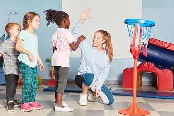 Kinder und Lehrerin geben sich ein High Five