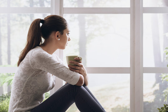 Young woman sitting next to the window and looking away