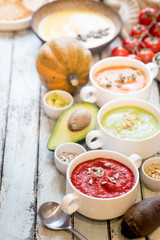 Variety of different colorful vegetable cream soups in a bowls. Concept of healthy eating or vegetarian food.