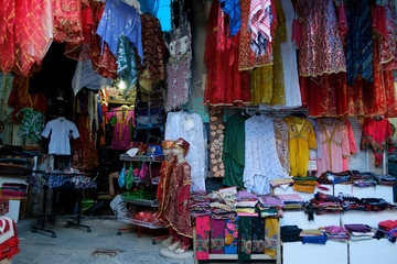 Rolls of fabric and textiles for sale stacked on shelves in shop, scarves for sale at the market, Traditional turkish, kurdish, arabic women dresses and costumes for sale at a market