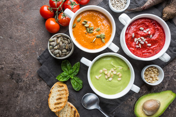 Variety of different colorful vegetable cream soups in a bowls, top view. Concept of healthy eating or vegetarian food.