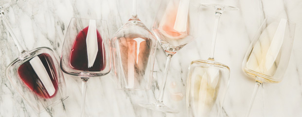 Tuinposter Wijn Flat-lay of red, rose and white wine in glasses and corkscrews over grey marble background, top view, wide composition. Wine bar, winery, wine degustation concept
