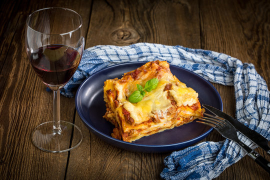 Piece of tasty hot lasagna with red wine.