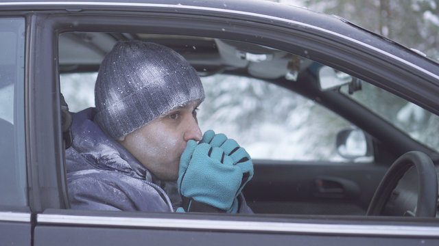 Frozen man sitting in the car and warm his hands
