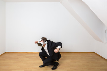 Mann mit VR Brille bewegt sich dynamisch im leeren Raum. Er testet seine virtuelle Einrichtung.