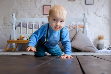 Beautiful blue-eyed baby crawling on the wooden floor