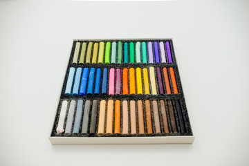 Close up view of bright colorful pastel chalks  on white background. Set of multicolored pastel crayons in openartist box on a white background, top view.
