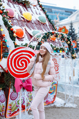 Pretty cute beautiful young woman with blond hair in a pink jacket and a knitted hat is stands on the street in a winter day. Fashionable girl walks outdoors and holds  Lollipop in the form of a heart