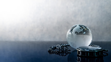 Global business concept. World globe crystal glass and silver pocket watch on glossy table. Time management and investment.