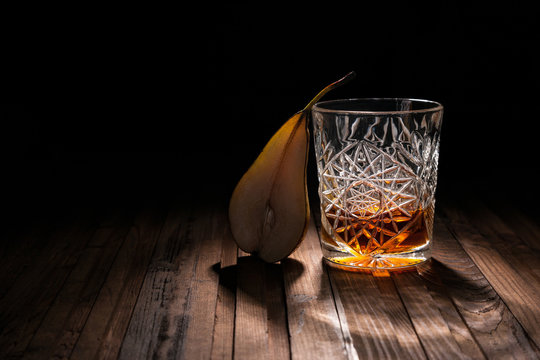 Crystal glass of whiskey on a wooden table on a black background. Snack for whiskey. Cheese, almonds, pear, apple, olives, orange peel.