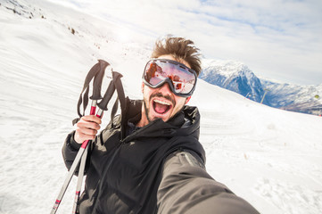 Handome skier in the snow taking a selfie on a mountain.