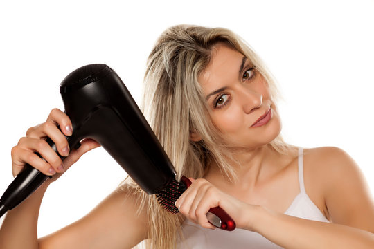 smiling young woman drying her hair with hair dryer on white backgrund