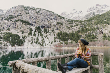 Woman on seat near wonderful lake between hills in snow