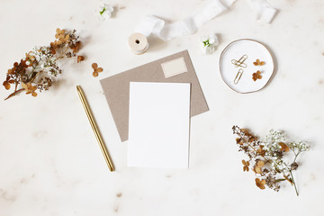Feminine winter wedding, birthday stationery mock-ups scene. Blank greeting card, kraft envelope, golden pen, dry hydrangea and gypsophila flowers. Marble stone table background. Flat lay, top view.