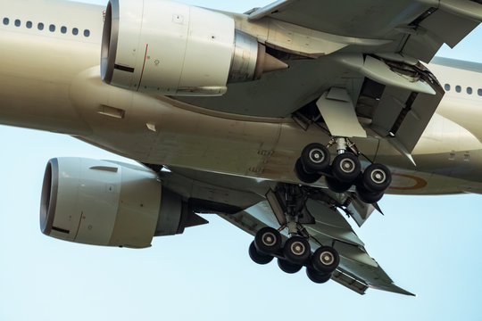 Closeup rubber wheels and chassis of commercial airline. Passenger plane landing or take off. Aerospace Engineering. Airplane flying on blue sky. Aircraft engine detail at landing or takeoff.