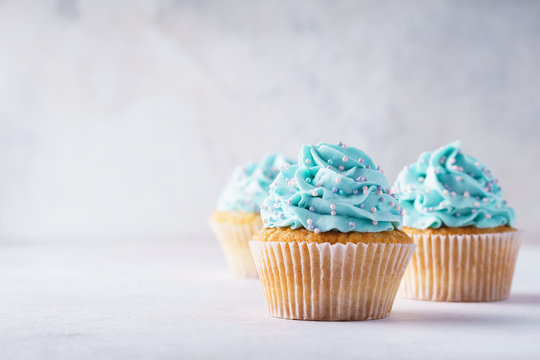Vanilla cupcakes with blue frosting decorated with sprinkles.