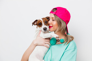 Beautiful young girl in pink cap and blue t-shirt with Jack Russell Terrier dog on white background.