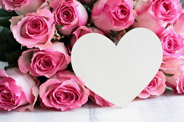 Beautiful retro soft pink rose flower background with wooden heart and room for text.