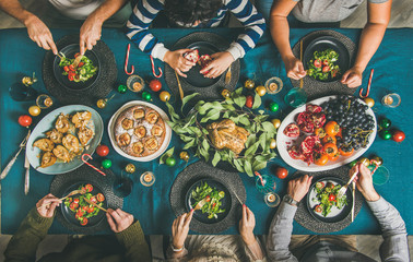 Company of friends of different ages gathering for Christmas or New Year party dinner at festive table. Flat-lay of people eating salads and fruits and celebrating holiday together, top view