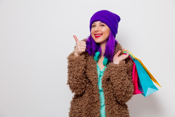 Beautiful young girl with purple hair in jacket holding shopping bags on white background.