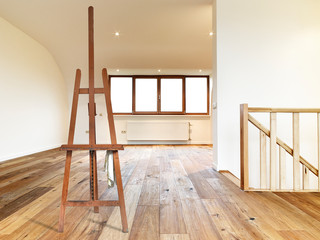 Painter's easel empty in a modern interior with wooden floor