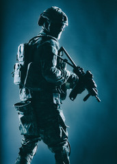 Army soldier in helmet, battle uniform with tactical ammunition, hiding face behind mask and glasses, looking back over shoulder, sneaking in darkness with service rifle in hand, low key, studio shoot
