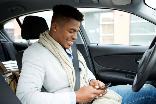 smiling young african american businessman looking at mobile phone while driving car