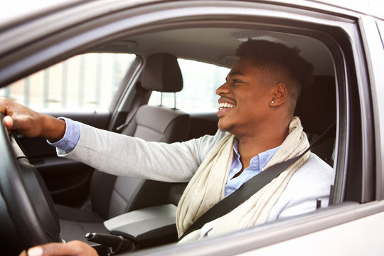 charming young african american man driving car in the city