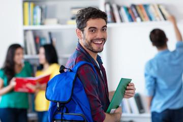 Lachender spanischer Student in der Uni-Bibliothek Wall mural