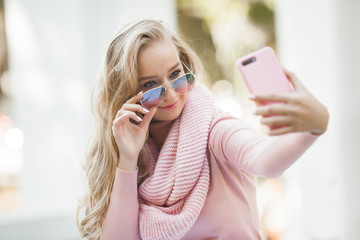 Attractive young woman making selfie outdoor. Casual girl talking on the cell phone in the park. Attractive young lady chatting with her friends by mobile.