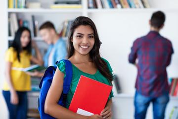 Lachende brasilianische Studentin in der Uni-Bibliothek
