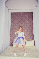 Photo of emotional little girl child in skirt