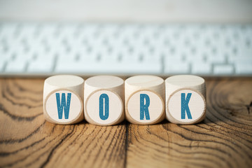 "cubes with word ""work"" in front of a computer keyboard on wooden background"