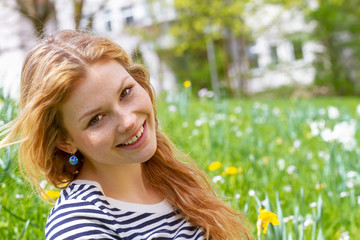 Happy girl with long red hair sitting on a flower meadow