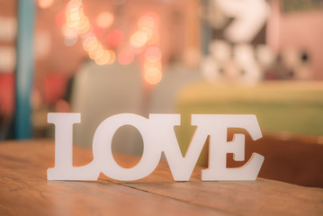 """The word """"Love"""" on wooden table with bokeh background. Vintage tone"""