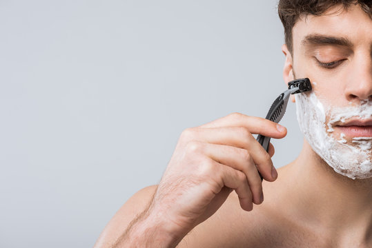 handsome young man foam on face shaving with razor, isolated on grey