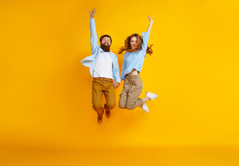 couple of emotional people man and woman jumping on yellow background.