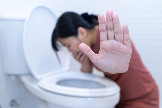 Woman hold hand and vomiting in toilet - sick concept