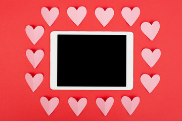 Flat lay of tablet computer with blank screen on red background with paper hearts. Valentine's Day concept