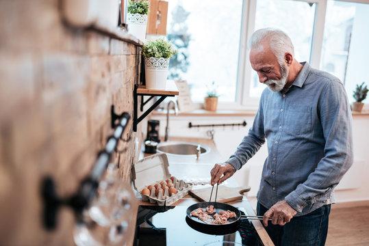 Smiling senior man cooking breakfast in modern cozy kitchen.