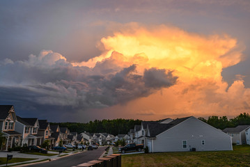 Neighborhood Houses Under a Colorful Sunset and Storm Clouds
