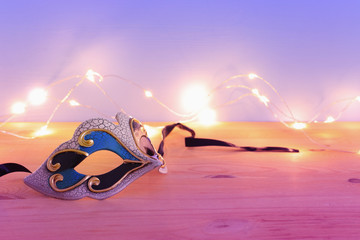 photo of elegant venetian, mardi gras mask over wooden table and garland gold lights.