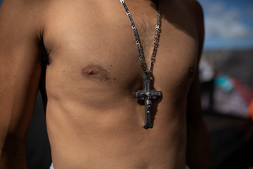 Mayno Enriques, from Honduras, part of a caravan of thousands of migrants from Central America travelling to the U.S., poses for a picture as he wears a cross at a temporary shelter in Tijuana