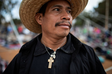 """Nicolas Alonso Sanchez, from Honduras, part of a caravan of thousands of migrants from Central America travelling to the U.S., poses for a picture as he wears a cross reading """"Salvation"""" at a temporary shelter in Tijuana"""