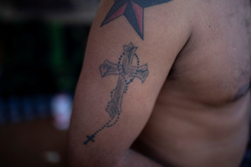 Nelson Mejia, from Honduras, part of a caravan of thousands of migrants from Central America travelling to the U.S., poses for a picture as he shows his tattoo of a cross before bathing at a temporary shelter in Tijuana