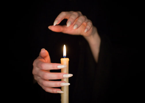 Candle and female witch hands with sharp pearl nails. Divination and witchcraft, low key.