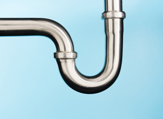 Stainless steel sink pipe on isolated on light blue background